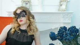 Jovem mulher bonita em uma máscara preta do carnaval, em um partido, em uma poltrona vermelha filme