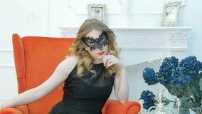 Jovem mulher bonita em uma máscara preta do carnaval, em um partido, em uma poltrona vermelha vídeos de arquivo