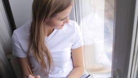 A jovem mulher bonita escreve em seu diário na janela vídeos de arquivo