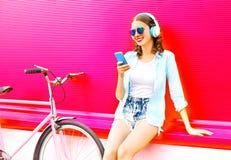 A jovem mulher bonita bonita escuta a música usando o smartphone imagens de stock royalty free