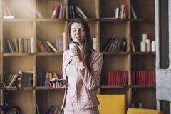 Jovem mulher bonita esperta nos fones de ouvido com um vidro do café Imagens de Stock Royalty Free
