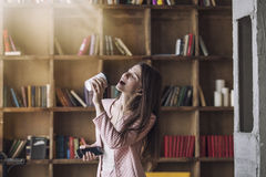 Jovem mulher bonita esperta nos fones de ouvido com um vidro do café Fotografia de Stock