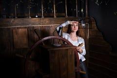A jovem mulher bonita está ao leme do navio e olha i fotografia de stock