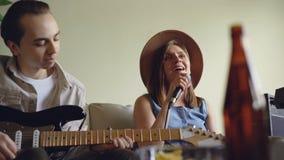 A jovem mulher bonita está cantando e seu guitarrista considerável do amigo está jogando a guitarra elétrica durante o ensaio em  filme