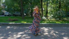 A jovem mulher bonita está dançando em um parque com um ramalhete das flores vídeos de arquivo