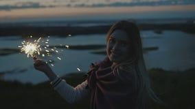 A jovem mulher bonita está em um monte alto com o chuveirinho no por do sol no movimento lento video estoque