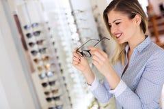 A jovem mulher bonita está escolhendo vidros novos na loja do sistema ótico fotos de stock royalty free