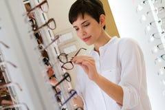 A jovem mulher bonita está escolhendo vidros novos na loja do sistema ótico fotografia de stock