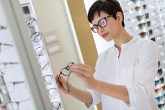 A jovem mulher bonita está escolhendo vidros novos na loja do sistema ótico imagem de stock