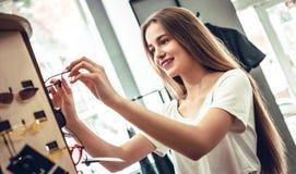 A jovem mulher bonita está escolhendo vidros novos na loja do sistema ótico foto de stock