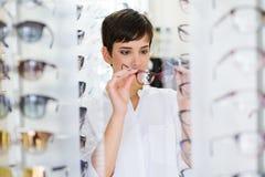 A jovem mulher bonita está escolhendo vidros novos na loja do sistema ótico imagem de stock royalty free