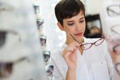 A jovem mulher bonita está escolhendo vidros novos na loja do sistema ótico fotos de stock
