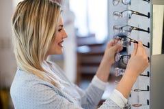 A jovem mulher bonita está escolhendo vidros novos na loja do sistema ótico foto de stock royalty free