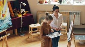 A jovem mulher bonita está guardando a paleta e flores de pintura sob a orientação do professor útil que está junto dentro filme