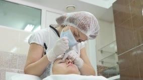 A jovem mulher bonita está obtendo a injeção do botox em seu mordente vídeos de arquivo