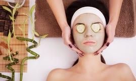 A jovem mulher bonita está obtendo a máscara facial da argila nos termas, encontrando-se com os pepinos nos olhos Foto de Stock