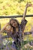 A jovem mulher bonita está sentando-se na grama com olhos fechados a Fotos de Stock Royalty Free