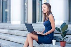 A jovem mulher bonita está trabalhando com um caderno Imagem de Stock
