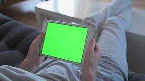 A jovem mulher bonita está usando uma tabuleta digital com a tela verde que senta-se no sofá em casa filme
