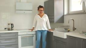 A jovem mulher bonita exulta o apartamento novo da compra A menina exulta em sua cozinha nova video estoque