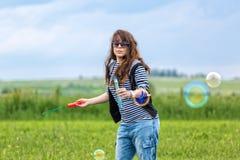 A jovem mulher bonita faz bolhas de sopro Fotografia de Stock Royalty Free