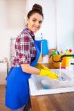 A jovem mulher bonita faz a limpeza da casa Ki da limpeza da menina imagem de stock