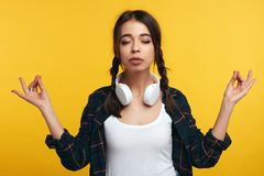 A jovem mulher bonita faz o sinal do mudra, relaxa após o dia de trabalho duro, mantém os olhos fechados, pratica a ioga contra o fotos de stock