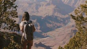 Jovem mulher bonita feliz com trouxa que anda acima ao cenário de surpresa da paisagem do verão do movimento lento de Grand Canyo video estoque