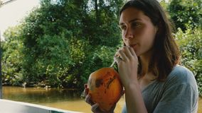 Jovem mulher bonita feliz que aprecia a navigação da bebida do coco no barco da excursão do safari ao longo do rio ensolarado da  filme