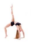A jovem mulher bonita flexível dútile faz exercícios atléticos, ginásticos na posição do caranguejo isolada sobre o fundo branco Fotografia de Stock