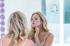 Jovem mulher bonita focalizada que olha si mesma no espelho do banheiro fotos de stock