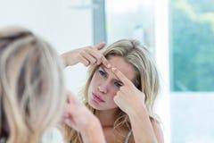 Jovem mulher bonita focalizada que olha si mesma no espelho do banheiro Fotos de Stock Royalty Free
