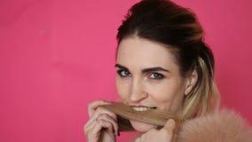 Jovem mulher bonita glamoroso em mordidas sensuais de um casaco de pele à moda seu cabelo no fundo cor-de-rosa filme