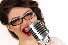 A jovem mulher bonita isolada no branco no estúdio na forma velha veste a representação do pinup e do estilo retro com o microfon Fotografia de Stock Royalty Free