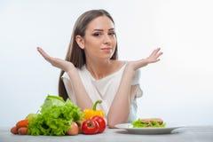 A jovem mulher bonita não conhece o que comer imagens de stock