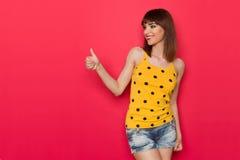 A jovem mulher bonita na camiseta de alças amarela dá o gosto Fotos de Stock