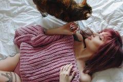 Jovem mulher bonita na camiseta de tamanho grande cor-de-rosa na cama fotografia de stock royalty free