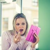 A jovem mulher bonita na camisola cor-de-rosa está pndo sobre o batom vermelho Fotografia de Stock