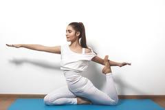 Jovem mulher bonita na ioga que levanta em um fundo do estúdio Fotos de Stock