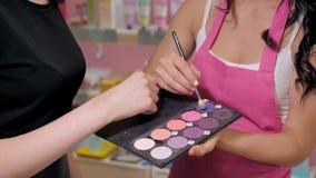 A jovem mulher bonita na loja da perfumaria escolhe cosméticos com cosultant Fotos de Stock Royalty Free