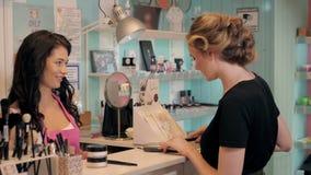 A jovem mulher bonita na loja da perfumaria escolhe cosméticos com cosultant Foto de Stock