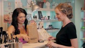 A jovem mulher bonita na loja da perfumaria escolhe cosméticos com cosultant Foto de Stock Royalty Free