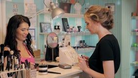 A jovem mulher bonita na loja da perfumaria escolhe cosméticos com cosultant Imagem de Stock