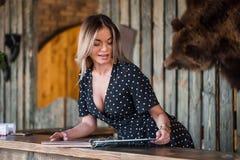 A jovem mulher bonita na recepção mostra o menu do serviço fotografia de stock royalty free