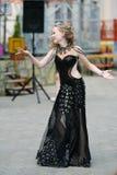Jovem mulher bonita na roupa de um estilo ocasional isolada sobre o fundo branco Moça que dança em público, dança árabe, menina imagens de stock royalty free