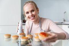 jovem mulher bonita no avental que prepara queques deliciosos com doce e sorriso imagem de stock