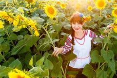 Jovem mulher bonita no bordado em um campo do girassol Foto de Stock