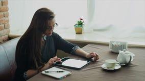 Jovem mulher bonita no café e utilização digital video estoque