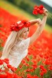 Jovem mulher bonita no campo da papoila da luz vermelha imagens de stock