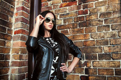 Jovem mulher bonita no casaco de cabedal e em óculos de sol pretos Imagem de Stock Royalty Free